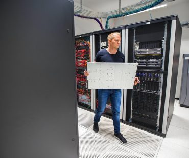 IT Consultant Carrying Blade Server While Walking In Datacenter